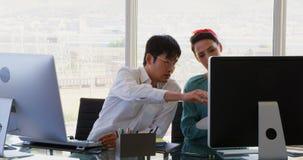 Μπροστινή άποψη των επιχειρηματιών αναμιγνύω-φυλών που συζητούν πέρα από τον υπολογιστή στο γραφείο στο γραφείο 4k φιλμ μικρού μήκους