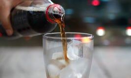 Μπροστινή άποψη, χύνοντας ποτό σόδας κόλας με τον πάγο και φυσαλίδα στοκ εικόνες