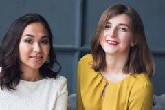 Μπροστινή άποψη δύο χαμογελώντας νέων θηλυκών φίλων που κάθονται στο καθιστικό στο σπίτι στοκ εικόνες