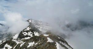 Μπροστινή εναέρια τοπ άποψη πέρα από το νεφελώδες δύσκολο χιονώδες βουνό στην ηλιόλουστη ημέρα με τα σύννεφα Ιταλικά βουνά ορών τ απόθεμα βίντεο