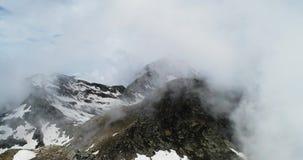 Μπροστινή εναέρια τοπ άποψη πέρα από το νεφελώδες δύσκολο χιονώδες βουνό στην ηλιόλουστη ημέρα με τα σύννεφα Ιταλικά βουνά ορών τ φιλμ μικρού μήκους