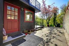 Μπροστινή κόκκινη πόρτα του μαύρου ξύλινου σπιτιού με την όψη κήπων. στοκ φωτογραφία