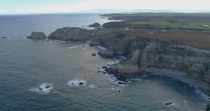 Μπροστινή μετακίνηση κατά μια γενική εναέρια άποψη κοντά στη θάλασσα που φτάνει πιό κοντά στην ακτή με πολλούς απότομους βράχους απόθεμα βίντεο