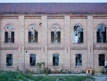 Μπροστινή πρόσοψη ενός εγκαταλειμμένου κτηρίου με τα σπασμένα παράθυρα Στοκ Εικόνες