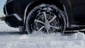 Μπροστινή ρόδα αυτοκινήτων στο βαθύ χιόνι στο χειμερινό τομέα λεπτομερή Στοκ Εικόνα