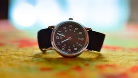 Μπροστινή σκοτεινή κινηματογράφηση σε πρώτο πλάνο wristwatch με το χρωματισμένο θολωμένο υπόβαθρο στοκ φωτογραφία με δικαίωμα ελεύθερης χρήσης
