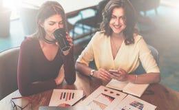 Μπροστινή όψη Δύο νέες εύθυμες επιχειρηματίες κάθονται στον καφέ στον πίνακα, καφές κατανάλωσης και εργασία από κοινού Στοκ εικόνα με δικαίωμα ελεύθερης χρήσης