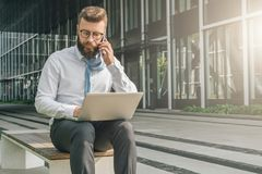 Μπροστινή όψη Ο νέος επιχειρηματίας στο άσπρο πουκάμισο κάθεται στο πάρκο στον πάγκο, ρίχνοντας το δεσμό του πέρα από τον ώμο του Στοκ εικόνες με δικαίωμα ελεύθερης χρήσης