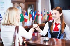 Μπροστινό γραφείο υποδοχής στο ξενοδοχείο Εργαζόμενος και φιλοξενούμενος στοκ εικόνες