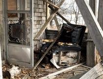 Μπροστινό μέρος ενός εγκαταλειμμένου σπιτιού με σχισμένο recliner επάνω Στοκ Εικόνα