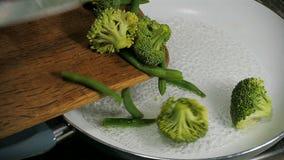 Μπρόκολο και πράσινη πτώση φασολιών στο τηγάνι κίνηση αργή απόθεμα βίντεο