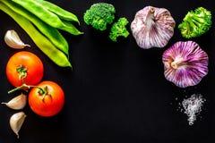 Μπρόκολο, σκόρδο, πράσινα φασόλια, ντομάτες και άλας σε ένα μαύρο υπόβαθρο Στοκ Φωτογραφίες