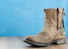Μπότα δέρματος μηχανικών όρφνωσης στην ξύλινη επιφάνεια και το μπλε backgrou Στοκ Εικόνες