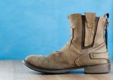 Μπότα δέρματος μηχανικών όρφνωσης στην ξύλινη επιφάνεια και το μπλε backgrou Στοκ εικόνες με δικαίωμα ελεύθερης χρήσης