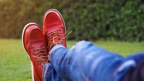 Μπότες ατόμων που στηρίζονται σε μια πράσινη χλόη με το μαλακό φως του ήλιου στοκ φωτογραφία
