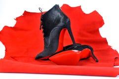 Μπότες γυναικών ` s χειροποίητες σε ένα κομμάτι του υλικού από το κόκκινο δέρμα Μίμησης παπούτσια εμπορικών σημάτων στοκ εικόνες
