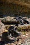 Μπότες και κάλτσες πεζοπορίας στο βράχο Στοκ Φωτογραφίες