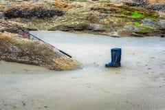 Μπότες και πόλος αλιείας στην παραλία Στοκ εικόνα με δικαίωμα ελεύθερης χρήσης