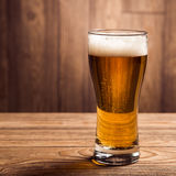 Μπύρα γυαλιού στο ξύλινο υπόβαθρο με το copyspace Στοκ Εικόνες