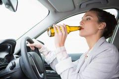 Μπύρα κατανάλωσης γυναικών οδηγώντας στοκ φωτογραφία
