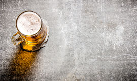 Μπύρα σε ένα γυαλί στην παλαιά επιφάνεια πετρών Στοκ εικόνα με δικαίωμα ελεύθερης χρήσης