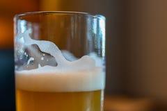 Μπύρα στην ψηλή κινηματογράφηση σε πρώτο πλάνο γυαλιού που πυροβολείται στο φραγμό Στοκ Εικόνες