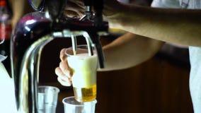 Μπύρα σχεδίων ατόμων από τη βρύση σε ένα πλαστικό φλυτζάνι Απομονωμένος σε ένα μαύρο υπόβαθρο φιλμ μικρού μήκους
