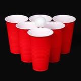 Μπύρα pong. Κόκκινες πλαστικές φλυτζάνια και σφαίρα αντισφαίρισης πέρα από το Μαύρο Στοκ φωτογραφία με δικαίωμα ελεύθερης χρήσης