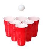 Μπύρα pong. Κόκκινες πλαστικές φλυτζάνια και σφαίρα αντισφαίρισης που απομονώνεται Στοκ Φωτογραφίες