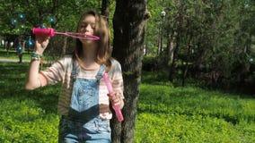 1 μπλε Ένα έφηβη στο πάρκο φυσά τις φυσαλίδες Συγκινήσεις ενός εφήβου απόθεμα βίντεο