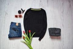 μπλε έξυπνη γυναίκα μόδας προσώπου έννοιας ομορφιάς makeup Μαύρες πουλόβερ και τουλίπες, τζιν παντελόνι, μαύρη τσάντα, γυαλιά ηλί Στοκ Εικόνες