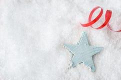 Μπλε αστέρι στο χιόνι με τον κόκκινο στρόβιλο κορδελλών Στοκ Εικόνες