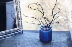 Μπλε βάζο με τους κλάδους δέντρων και έναν καθρέφτη Στοκ Φωτογραφία