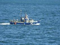 Μπλε βάρκα που πλέει στον ωκεανό Στοκ Εικόνες