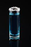 Μπλε βλασταημένο βατόμουρο ποτό με τα διακοσμητικά ξέσματα καρύδων στην κορυφή Ένα οινοπνευματώδες ποτό σε ένα μαύρο υπόβαθρο αντ Στοκ Εικόνες