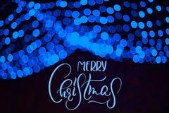 Μπλε γιρλάντα θαμπάδων στο ντεκόρ Winter Park με τη Χαρούμενα Χριστούγεννα κειμένων Καλλιγραφία και εγγραφή Στοκ Εικόνες