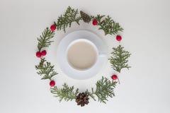 μπλε γυαλί σύνθεσης Χριστουγέννων μπιχλιμπιδιών Το φλιτζάνι του καφέ με τους πράσινους κλαδίσκους thuja και κόκκινο άγριο αυξήθηκ Στοκ φωτογραφία με δικαίωμα ελεύθερης χρήσης