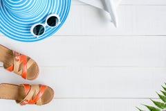 Μπλε γυαλιά ηλίου και παπούτσι καπέλων στον άσπρο ξύλινο πίνακα Στοκ εικόνα με δικαίωμα ελεύθερης χρήσης