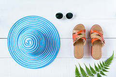 Μπλε γυαλιά ηλίου και παπούτσι καπέλων στον άσπρο ξύλινο πίνακα Στοκ Φωτογραφία
