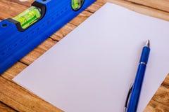 Μπλε επίπεδο οικοδόμησης υποβάθρου και ένα φύλλο του εγγράφου στοκ εικόνες