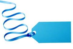 Μπλε ετικέττα ή ετικέτα δώρων με τη μακριά σγουρή κορδέλλα που απομονώνεται στο άσπρο υπόβαθρο Στοκ φωτογραφίες με δικαίωμα ελεύθερης χρήσης