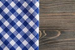 Μπλε ελεγμένη πετσέτα στην γκρίζα ξύλινη επιτραπέζια χλεύη επάνω Στοκ Εικόνες