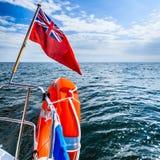Μπλε θάλασσα. Άποψη από τη γέφυρα sailboat γιοτ της βρετανικής σημαίας lifebuoy. Ταξίδι. Στοκ Εικόνες