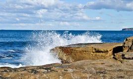 Μπλε θάλασσα και άσπρα κύματα που χτυπούν τους βράχους Στοκ Φωτογραφία