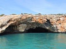 Μπλε θάλασσα και κόκκινοι βράχοι με τις σπηλιές Στοκ Φωτογραφία