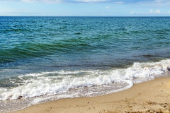 Μπλε θάλασσα με τα κύματα οριζόντων και αφρού στην παραλία άμμου, backgro Στοκ Φωτογραφίες