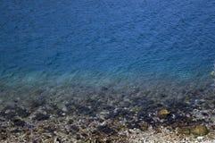 Μπλε θάλασσα με τους βράχους Στοκ Φωτογραφία