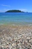 Μπλε θαλάσσιο νερό, χαλίκια και νησί Στοκ φωτογραφίες με δικαίωμα ελεύθερης χρήσης