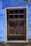 Μπλε διαστρεβλωμένο ξύλο παράθυρο σε έναν τοίχο χρωμάτων Στοκ Φωτογραφία
