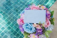 Μπλε κάρτα εγγράφου πέρα από τη ζωηρόχρωμη ανθοδέσμη λουλουδιών με το διάστημα στο υπόβαθρο πισινών στοκ εικόνες